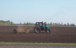 Tractor plowing the ground. Tractor plowing land in spring Stock Photography