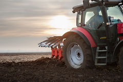 Tractor Plowing In Sunset Stock Photo