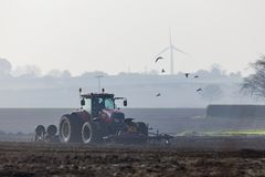 Tractor plowing the land in the morning stock photo