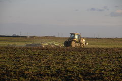 Tractor plowing plow the field. Tilling the soil in the fall after harvest. The end of the season Royalty Free Stock Photo
