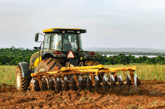 Tractor plowing and preparing the soil. Royalty Free Stock Images