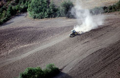 Tractor plowing a sloping field Stock Photo