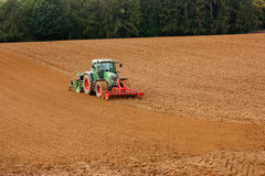 A tractor plowing soil. An agricultural landscape with a tractor plowing the soil closed to Bad Pyrmont in Germany Stock Photo