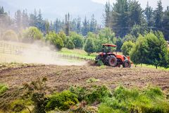Tractor plowing to sow yellow potato Stock Image