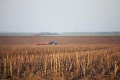 Tractor plows autumn field Stock Photos