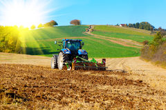 Tractor plows a field. In the spring, with sunlight Royalty Free Stock Photos