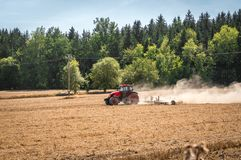 Tractor plows a field - agriculture and agronomy concept. Red tractor plows a field - agriculture and agronomy concept stock photography