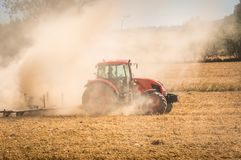 Tractor plows a field - agriculture and agronomy concept. Red tractor plows a field - agriculture and agronomy concept stock photo
