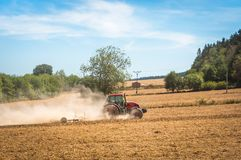 Tractor plows a field - agriculture and agronomy concept. Red tractor plows a field - agriculture and agronomy concept royalty free stock image