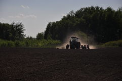 The tractor plows the field. In a bright sunny day boils Agricultural life Stock Photo
