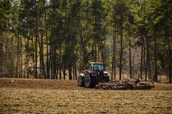 Tractor plows the field. Spring, the beginning of the planting season. Big tractor rides on the field stock images