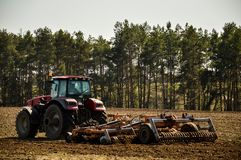 Tractor plows the field. Spring, the beginning of the planting season. Big tractor rides on the field stock photography