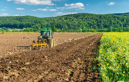 Tractor plows a field in the summer Royalty Free Stock Images
