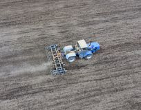 The tractor plows the field. Under sowing, the soil is loosened. On the field Stock Photography