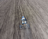 The tractor plows the field. Under sowing, the soil is loosened on the field. The tractor plows the field. Under sowing, the soil is loosened on the field Royalty Free Stock Images
