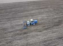 The tractor plows the field. Under sowing, the soil is loosened on the field. The tractor plows the field. Under sowing, the soil is loosened on the field Royalty Free Stock Photo