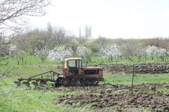 Tractor plows p04. Nature,  a spring awakening, blue sky, tractor plows, flowering trees, apricot trees, field Stock Image