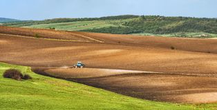 Tractor plows the spring field before a seeding. Ukrainian valley, Europe Stock Photos