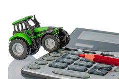 Tractor, pluma roja y calculadora Imágenes de archivo libres de regalías