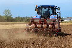 Tractor with  a pneumatic seed drill machine on a freshly plowed field in summertime.  royalty free stock image