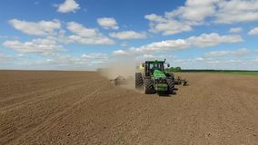 Sowing. A tractor with a pneumatic seeder sows a field stock footage