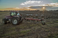 Tractor preparing field. Agricultural landscape with fresh plowed field, and suneset in the background Stock Photo