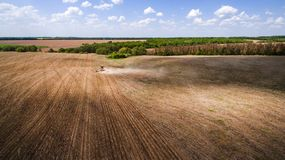 Tractor preparing land for sowing sixteen rows aerial, concept of cultivation, sowing, plowing field, tractor and production autom. Ation, place for text stock image