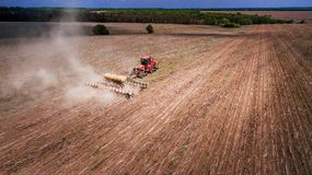 Tractor preparing land for sowing sixteen rows aerial, concept of cultivation, sowing, plowing field, tractor and production autom. Ation, place for text royalty free stock image