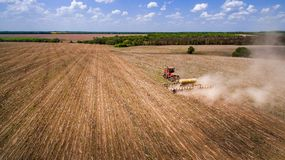 Tractor preparing land for sowing sixteen rows aerial, concept of cultivation, sowing, plowing field, tractor and production autom. Ation, place for text stock photos