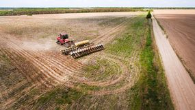 Tractor preparing land for sowing sixteen rows aerial, concept of cultivation, sowing, plowing field, tractor and production autom. Ation, place for text royalty free stock photography
