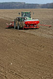 Tractor preparing land for sowing. Tractor with cultivator handles field before planting. Preparing land for sowing at spring Royalty Free Stock Photography