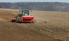 Tractor preparing land for sowing. Tractor with cultivator handles field before planting. Preparing land for sowing at spring Royalty Free Stock Image