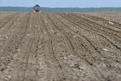 Tractor preparing land for sowing. Tractor with cultivator handles field before planting. Preparing land for sowing at spring Royalty Free Stock Images
