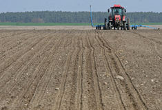 Tractor preparing land for sowing. Tractor with cultivator handles field before planting. Preparing land for sowing at spring. Farmer in tractor royalty free stock images