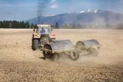 Tractor pulling heavy metal roller on dry field, dust behind and. Black smoke above, mountains in back. Spring ground preparation Stock Photography