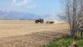 Tractor pulling heavy metal roller over dry field, with mountain. S, little bit snow on top, in background. Spring field preparation Stock Photo