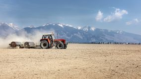 Tractor pulling heavy metal roller over dry field on a nice spri. Ng day with mountains in background. Soil preparation Royalty Free Stock Photography