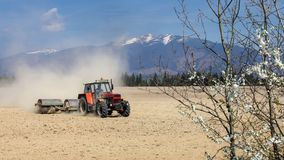 Tractor pulling heavy metal roller, when preparing dry field in. The spring, dust cloud behind, with mountains in the background Stock Photography
