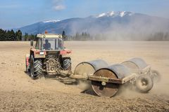 Tractor pulling heavy metal rollers on a dry field with mountain. S in background. Spring ground preparation Royalty Free Stock Photography