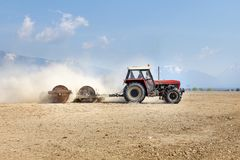Tractor pulling heavy metal rollers, preparing field in spring,. With mountains in background Stock Photo