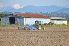 Tractor Pulling Hoe in Mountain Farm. Profile view of a tractor and hoe plowing the field as Spring seeding gets in full swing Stock Photos
