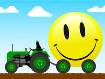Tractor pulling a huge smiley face Stock Image