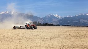 Tractor pulling metal rollers over dry field with mountains in b. Ackground. Spring soil preparation Stock Photo