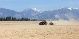 Tractor pulling rollers over dry fields in spring, mountains wit stock photo