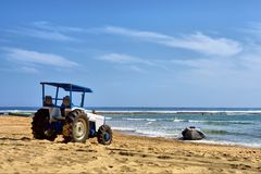 Tractor pulls a boat from water. On beach. Shot in Sodwana Bay Nature Reserve, KwaZulu-Natal province, Southern Mozambique area, South Africa Stock Images