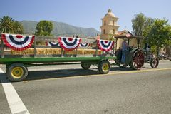 Tractor pulls decorated float down main street during a Fourth of July parade in Ojai, CA Stock Images