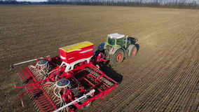 The tractor pulls a large seeder across the field. Sowing campaign in early spring, rural landscape. Concept - modern