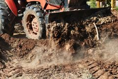 Tractor push clot soil after pour from truck. Detail tractor push clot soil after pour from truck Stock Photo