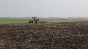Tractor que ara el campo, agricultura metrajes