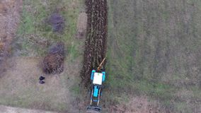 Tractor que ara el jardín Arado del suelo en el campo almacen de metraje de vídeo